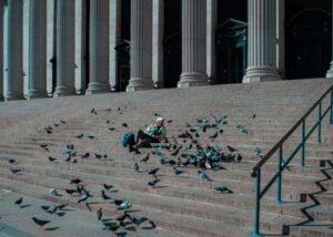 Hombre sentado con palomas